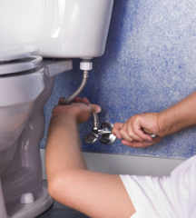 Plumbing contractor tightens an intake line on an American Standard comfort height toilet